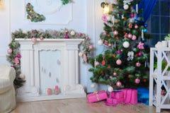 Imagen de la chimenea y del árbol de navidad adornado con el regalo Fotos de archivo
