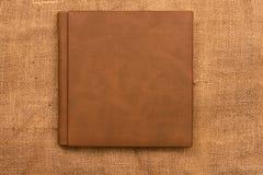 Imagen de la cubierta de cuero marrón del álbum de foto en fondo del yute K Fotografía de archivo