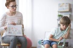 Imagen de la demostración del psicoterapeuta al muchacho imagen de archivo libre de regalías