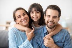 Imagen de la familia de los padres sonrientes del abrazo divertido del preescolar fotos de archivo libres de regalías