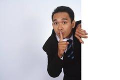 Imagen de la foto del hombre de negocios asiático hermoso que lleva a cabo una muestra en blanco con gesto silencioso Fotografía de archivo libre de regalías