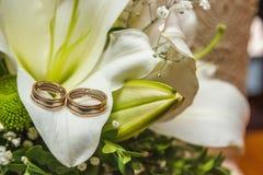 Imagen de la foto de los anillos de la obra clásica de un oro de la boda de la novia y del novio en una tabla blanca, con un ramo fotografía de archivo