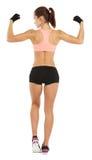 Imagen de la longitud entera de la mujer deportiva joven que muestra su aislador del bíceps imagenes de archivo