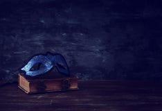 Imagen de la máscara veneciana azul real elegante sobre el libro viejo del vintage en fondo de madera oscuro delantero imagenes de archivo