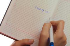 Imagen de la mano femenina con la pluma que lleva a cabo la lista de compras Imagen de archivo