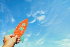 Imagen de la mano masculina que sostiene un cohete contra el cielo imaginación y concepto del éxito fotografía de archivo libre de regalías