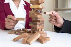 Imagen de la mano que lleva a cabo el juego de madera de los bloques a crecer del negocio Riesgo de plan de gestión y de la estra imagenes de archivo