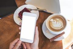 Imagen de la maqueta de las manos que sostienen el smartphone blanco con la pantalla en blanco, la tableta, el ordenador portátil Foto de archivo libre de regalías