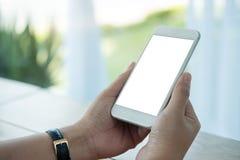 Imagen de la maqueta de las manos que sostienen el teléfono móvil blanco con la pantalla en blanco en la tabla Fotos de archivo libres de regalías