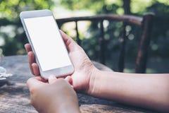 Imagen de la maqueta de las manos que sostienen el teléfono móvil blanco con la pantalla en blanco en la tabla de madera del vint Fotografía de archivo