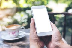 Imagen de la maqueta de las manos que sostienen el teléfono móvil blanco con la pantalla en blanco en la tabla de madera del vint Imagen de archivo libre de regalías