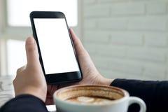 Imagen de la maqueta de las manos que sostienen el teléfono móvil negro con la pantalla blanca en blanco con una taza de café Fotografía de archivo
