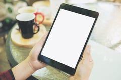Imagen de la maqueta de las manos que sostienen la PC negra de la tableta con la pantalla blanca en blanco con las tazas de café  Imagen de archivo