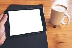 Imagen de la maqueta de la mano que sostiene la PC negra de la tableta con la pantalla blanca en blanco en una taza del papel neg imagen de archivo libre de regalías
