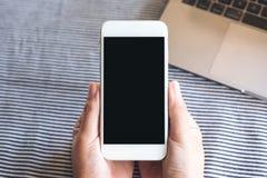 Imagen de la maqueta de la visión superior de las manos que sostienen el teléfono móvil blanco con la pantalla de escritorio negr Imagen de archivo libre de regalías