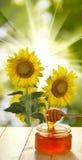 Imagen de la miel en la tabla contra el primer del fondo de las flores Fotografía de archivo libre de regalías
