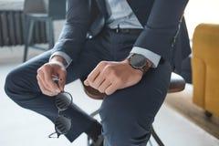 Imagen de la moda del primer de un hombre de negocios que se está sentando en la silla y está sosteniendo las gafas de sol foto de archivo libre de regalías