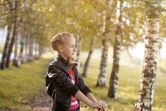 Imagen de la muchacha adorable que presenta en arboleda del abedul Foto de archivo