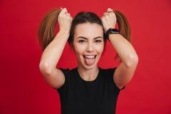 Imagen de la muchacha adulta graciosamente 20s en la camiseta negra que juega alrededor Fotos de archivo
