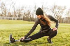 Imagen de la muchacha atlética discapacitada morena en ropa de deportes, haciendo el SP foto de archivo