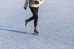 Imagen de la muchacha del adolescente de las piernas que está patinando en la pista de hielo Fotografía de archivo