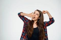 Imagen de la muchacha divertida joven que bosteza y vestida en camisa de tela escocesa Imagen de archivo