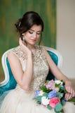 Imagen de la muchacha elegante que se sienta en butaca retra del estilo Modelo joven moreno imagen de archivo