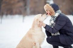 Imagen de la muchacha en el abarcamiento negro Labrador de la chaqueta en parque nevoso Fotos de archivo libres de regalías