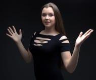 Imagen de la muchacha en vestido negro con las manos abiertas Fotografía de archivo
