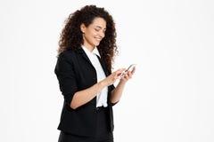 Imagen de la muchacha rizada alegre del negocio que mira su teléfono Imagenes de archivo