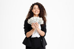Imagen de la muchacha rizada alegre del negocio que sostiene el dinero Foto de archivo