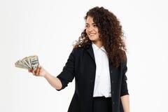 Imagen de la muchacha rizada alegre del negocio que sostiene el dinero Fotografía de archivo libre de regalías