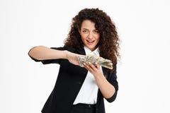 Imagen de la muchacha rizada alegre del negocio que sostiene el dinero Imágenes de archivo libres de regalías