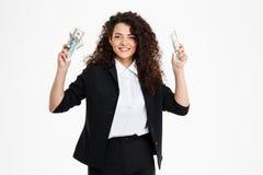 Imagen de la muchacha rizada alegre del negocio que sostiene el dinero Fotos de archivo libres de regalías