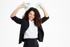Imagen de la muchacha rizada alegre del negocio que sostiene el dinero Imagenes de archivo