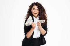 Imagen de la muchacha rizada alegre del negocio que sostiene el dinero Imagen de archivo