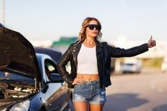 Imagen de la muchacha rubia joven que para el coche en la calle fotos de archivo