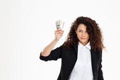 Imagen de la muchacha seriamente rizada del negocio que sostiene el dinero Fotos de archivo libres de regalías