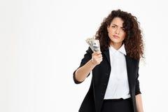 Imagen de la muchacha seriamente rizada del negocio que sostiene el dinero Foto de archivo libre de regalías