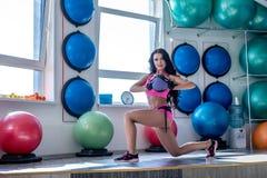 Imagen de la mujer agradable que presenta mientras que ejercita en gimnasio Imágenes de archivo libres de regalías