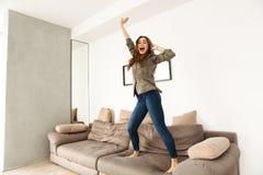 Imagen de la mujer alegre 20s en el baile de la ropa informal en el sofá Fotografía de archivo