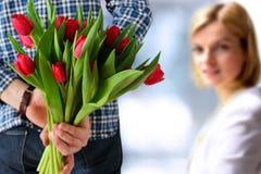 Imagen de la mujer asombrosamente del hombre joven con las flores fotografía de archivo libre de regalías