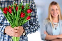 Imagen de la mujer asombrosamente del hombre joven con las flores Fotos de archivo