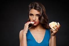 Imagen de la mujer atractiva en vestido azul que come el pedazo de torta Foto de archivo libre de regalías
