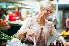 Imagen de la mujer madura en las verduras de compra del mercado fotografía de archivo