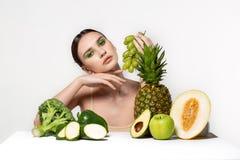 Imagen de la mujer morena joven hermosa con las frutas y verduras en la tabla, sosteniendo las uvas verdes a disposici?n aisladas fotos de archivo libres de regalías