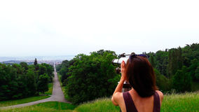 Imagen de la mujer que considera a través de los prismáticos el paisaje de la ciudad Fotografía de archivo