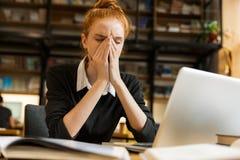 Imagen de la mujer seria del pelirrojo que estudia, mientras que se sienta en el escritorio i imágenes de archivo libres de regalías