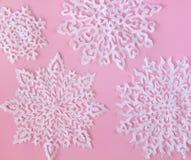 Imagen de la Navidad o del Año Nuevo - copos de nieve blancos hechos del papel, aislado en fondo rosado Fotos de archivo libres de regalías