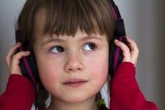 Imagen de la niña bonita feliz del niño con los auriculares grandes en casa La muchacha alegre del niño que escuchaba la música e Imagen de archivo